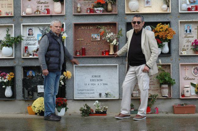 (Izq. a der.) Eloy Jaúregui y Plácido Deplano (amigo del poeta) en visita al nicho de Jorge E. Eielson en el cementerio Barisardo en Cerdeña (Italia),